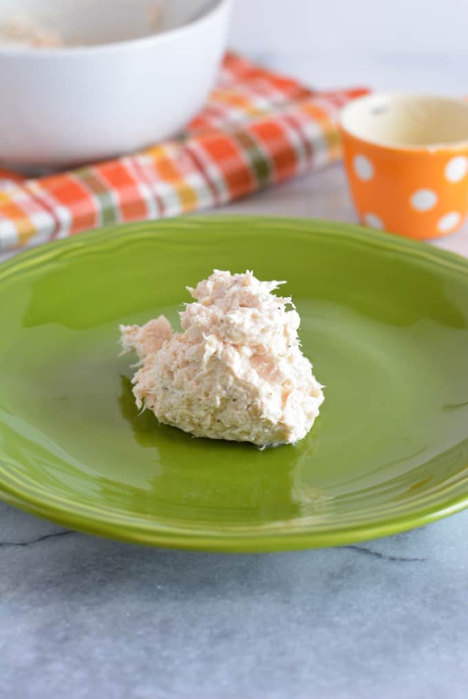 A spoonful of creamy chicken salad on a green plate.