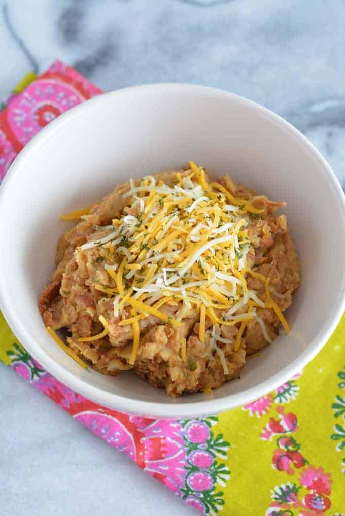Low-fat refried beans in a white bowl topped with shredded cheese.